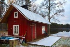 Das finnische Haus der roten Farbe auf dem See Stockbild
