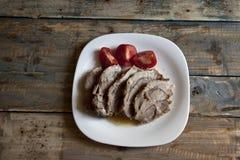 Das Fleisch, das auf einer weißen Platte gebacken wurde, schnitt in Stücke stockfoto