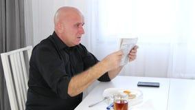 Das Fleisch fressende Mittagessen las Zeitungs-schlechte Nachrichten und gestikuliert nervös und gereizt stock footage