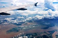 Das Flugzeug flog in den blauen Himmel und in die weißen Wolken Stockfotos