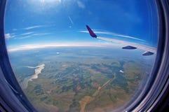 Das Flugzeug flog in den blauen Himmel und in die weißen Wolken Stockfotografie