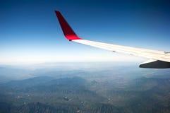 Das Flugzeug flog in den blauen Himmel und in die weißen Wolken Lizenzfreies Stockbild