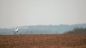Das Flugzeug ist eine Ernte, die Staubtuch über ein Feld fliegt und das Düngemittel sprüht stock footage