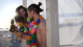 Das formschöne Mädchen, das für Manncocktail auf Strand, junges Paar der Sommerferien in Hawaii geholt wird, Mädchen kommt zum Ke stock video footage