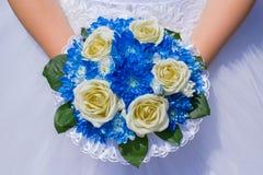 Das Foto der Braut in einem weißen Kleid mit einem Hochzeitsblumenstrauß in ihr Stockfoto