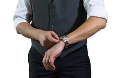 Das Foto des Geschäftsmannes in einem weißen Hemd und in einer grauen Weste der Mann umklammert Stunden Stockbilder