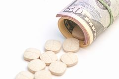Das Foto vieler Dollar eingewickelt und die Tablettenlüge, die nahe auf Weiß lokalisiert werden, zeigen zahlende Medizin und Korr Stockfotografie