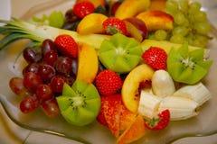 Das Foto wird schön geschnitten und eine köstliche tropische Frucht verzierte, die auf einem transparenten Glasteller ausgebreite Stockfotografie