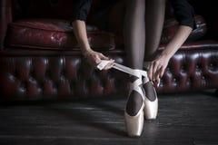 Das Fragment der Hände des Mädchens, pointe Schuhe binden stockfotos