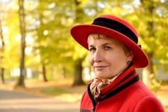 Das Frau ` s Porträt in einem roten Hut auf der Herbststraße Stockfotografie