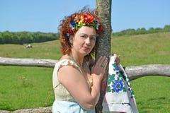 Das Frau ` s Porträt mit einem Kranz auf dem Haupt- und bunten Schal in den Händen über einen Zaun Lizenzfreie Stockfotos