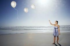 Das Frauen-Lassen gehen von den Ballonen auf Strand Stockfoto