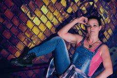 Das Frauen ` s Modell sitzt vor der Backsteinmauer Lizenzfreies Stockbild