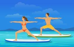 Das Frauen- und Mannhandeln steht oben, schaufelnd Yoga auf Radschaufel an der Küste Lizenzfreies Stockfoto