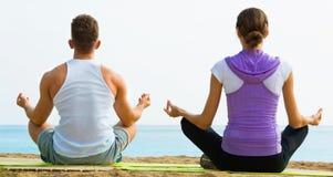 Das Frauen- und Mannsitzen im Schneidersitz tun Yogahaltungen auf Strand Stockfotografie