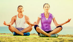 Das Frauen- und Mannsitzen im Schneidersitz tun Yogahaltungen auf Strand Stockfoto