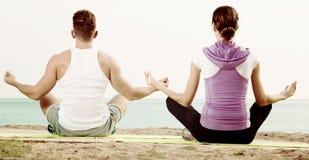 Das Frauen- und Mannsitzen im Schneidersitz tun Yogahaltungen auf Strand Lizenzfreie Stockfotografie