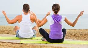Das Frauen- und Mannsitzen im Schneidersitz tun Yogahaltungen auf Strand Lizenzfreies Stockfoto