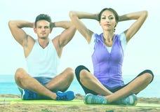 Das Frauen- und Mannsitzen im Schneidersitz tun Yogahaltungen auf Strand Lizenzfreies Stockbild