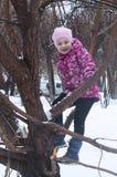 Das frohe Mädchen sitzt auf einem Baum im Winter Lizenzfreie Stockfotografie