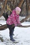 Das frohe Mädchen sitzt auf einem Baum im Winter Stockbild