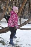 Das frohe Mädchen sitzt auf einem Baum im Winter Stockfotografie