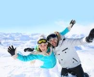 Das frohe Paar, das Spaß auf dem Ski hat, neigt sich lizenzfreie stockfotografie
