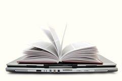 Das geöffnete Buch, das auf den Laptop legt Lizenzfreie Stockfotografie