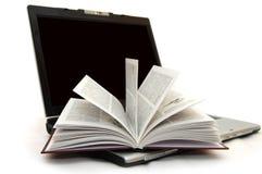 Das geöffnete Buch, das auf Laptop legt Stockfoto