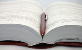 Das geöffnete Lehrbuch mit Feder Lizenzfreie Stockfotos