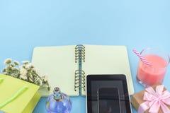 Das geöffnete Notizbuch für Aufzeichnungen liegt auf der Oberfläche des Cocktailrosaglasrohrblumenstraußchrysanthemenparfümtablet Stockbild