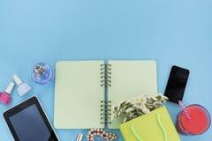 Das geöffnete Notizbuch für Aufzeichnungen liegt auf der Oberfläche des Cocktailrosaglasrohrblumenstraußchrysanthemenparfümtablet Stockfoto