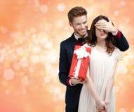 Das Geben eines Weihnachtsgeschenkmannes schließt Augen seiner Freundin Stockbild