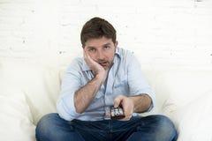 Das gebohrte aufpassende Fernsehen des Mannes, das auf dem Sofa hält Fernbedienung sitzt, ermüdete Haben nicht des Spaßes Lizenzfreies Stockbild