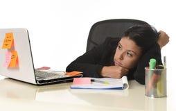 Das gebohrte lateinische Geschäftsfrauarbeiten ermüdete am Bürocomputertisch, der erschöpft schaut Stockfoto