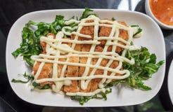 Das gebratene Huhn der Zitrone, das mit Majonäse überstiegen wird, verzieren weiße Platte und vegetable= Stockfotos