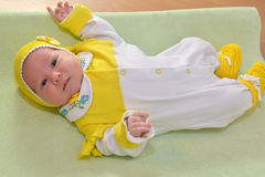 Das gekleidete Baby liegt auf einer kleinen Tabelle Lizenzfreie Stockfotografie