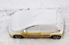 Das gelbe Auto unter dem Schnee Lizenzfreie Stockbilder