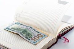 Das Geld ist auf einem offenen Notizbuch stockfotografie