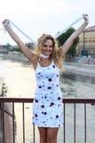 Das gelockte blonde auf der Brücke stehende und vortäuschende Mädchen ist sie S Lizenzfreies Stockbild
