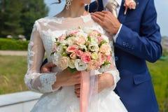 Das gerade verheiratete Paar, das umfasst werden, und die Braut, die schöne Hochzeit hält, blüht lizenzfreie stockfotos