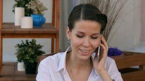 Das Geschäftsfrausitzen entspannte sich Café am im Freien, das unter Verwendung ihres Handys spricht stock video