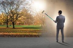 Das Geschäftsmannmalerei-Naturbild mit Rollenbürste stockfotografie