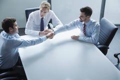 Das Geschäftsmannrütteln überreicht die Tabelle im Büro stockfotos