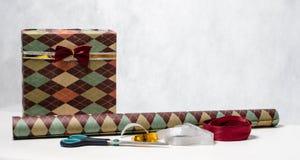 Das Geschenk der Männer in einem schönen Paket, in einem Packpapier, in Scheren und in einem Band Stockfoto