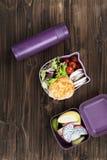 Das geschmackvolle Kotelett, das auf Salat liegt, verlässt in der Brotdose Stockfotos