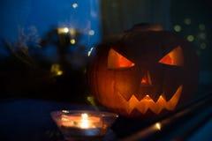 Das geschnitzte Gesicht des Kürbises glühend auf Halloween auf grünem Hintergrund Lizenzfreie Stockfotografie