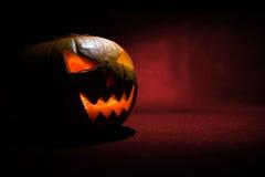 Das geschnitzte Gesicht des Kürbises glühend auf Halloween auf rotem Hintergrund Stockfoto
