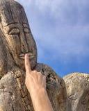 Das Gesicht, das im Holz mit der Frauenhand auf Lippen geschnitzt wurde, schnitzte Zahl Stockfotografie