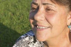 Das Gesicht der älteren Frau wird durch einen Abschluss oben fotografiert. Stockfotografie